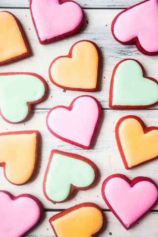 Red Velvet Valentine's Day heart-shaped cookies are arranged in a single layer on a tray. The cookies have pink, yellow, or green frosting. Photo credit to Baking a Moment blog.