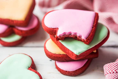 A few stacks of the red velvet heart-shaped Valentine's Day cookies are shown. The front stack has a cookie with pink frosting on top with a bite taken out of it. Photo credit to the Baking a Moment blog.