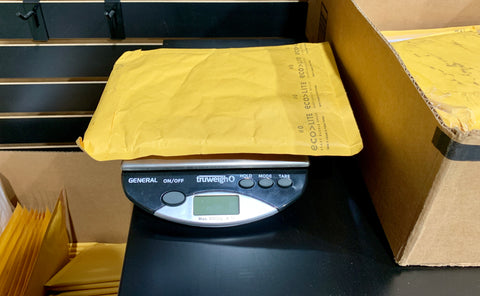 The Truweigh General bench scale is weighing a yellow padded envelope that is being prepared for shipment.