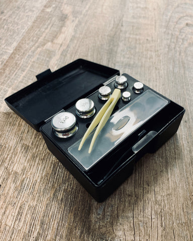 The 6-piece black Truweigh calibration weight kit sits on a wood floor with the tweezers positioned on top.