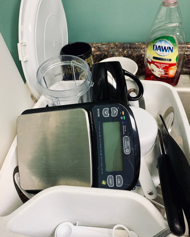 The Truweigh Wave digital washdown scale sits on its side in a drying rack of dishes after being washed.