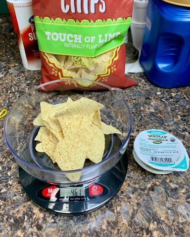 The Truweigh Vortex kitchen scale sits on a granite counter. It has a serving of lime tortilla chips being weighed, and an individual guacamole pack is next to the scale with the seal still in tact. The bag of chips is behind the scale.