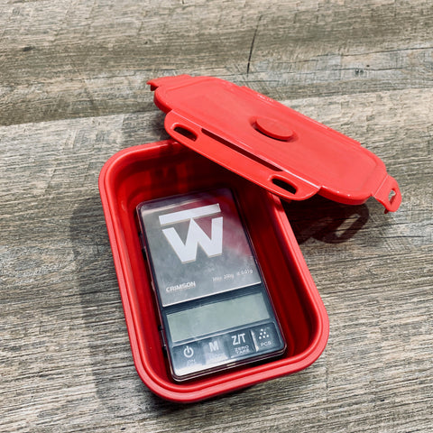 Crimson digital food scale sits in its collapsible red silicone bowl, with the locking cover leaned up against the bowl.