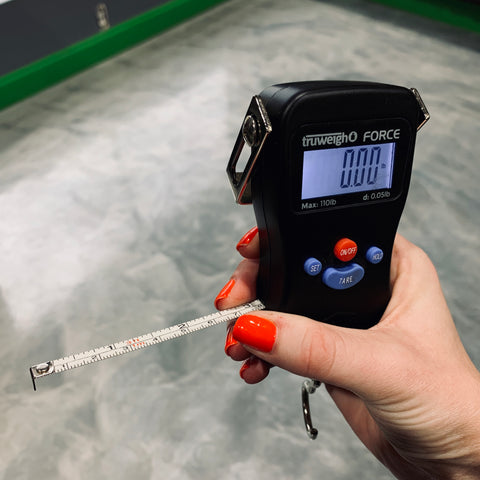A female hand with red nail polish holds the Truweigh Force Digital Hanging scale indoors with the tape measure extended, and held between her thumb and middle finger.