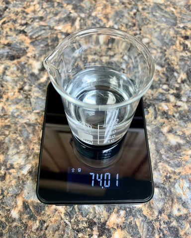 A small beaker of water is sitting on top of a Truweigh Storm digital scale. The scale is all black with gray numbers reading the weight 74.01 grams. The scale is on a Formica counter top