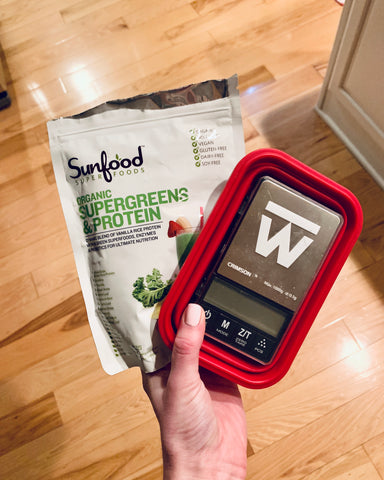 The Truweigh Crimson digital food scale is turned off, cover on inside the collapsed silicone weighing bowl. A female hand holds the scale and a packet of superfood protein powder in her hand above a wood floor.
