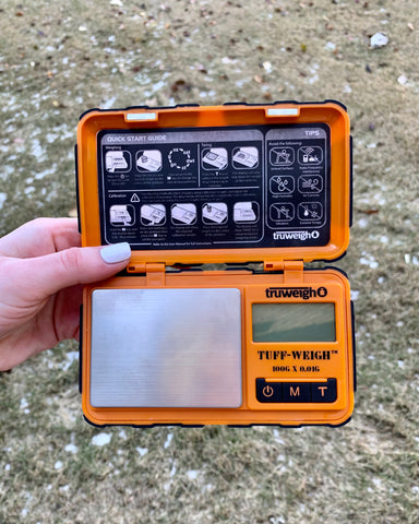 A white female hand holds the orange Truweigh Tuff-Weigh digital scale with the cover open showing the entire scale. The scale is held outside against a grassy background.