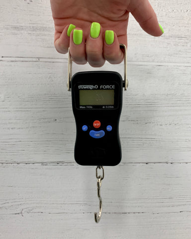 A female hand with bright green nail polish holds the Truweigh Force Digital Hanging scale in front o f a white wooden background. The scale is held by her second, middle and ring fingers.