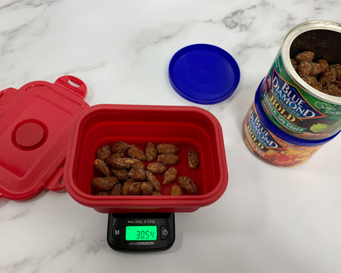 The Truweigh Crimson digital food scale is weighing a portion of almonds in the collapsible silicone bowl. Two cans of almonds are stacked to the right, the top can is open with the lid sitting next to the cans. Everything sits on a white marble surface.