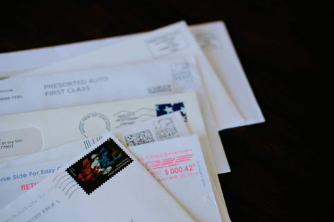 Stack of letters spread out to reveal the postage corners of each. 7 letters laying on a dark wood background