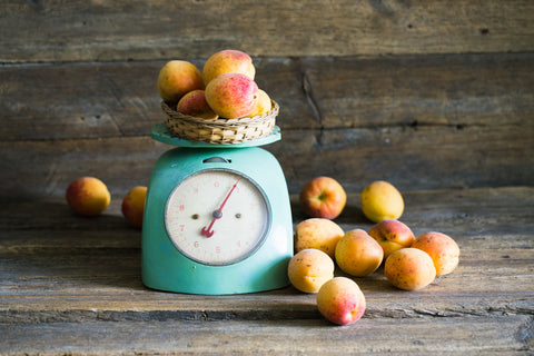 A light teal spring balance scale holds several peaches with a pile of peaches sitting next to it. The scale and fruits sit on a rustic wood counter top in front of the same wood background.