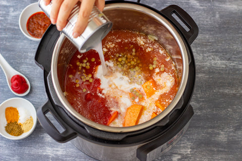 A hand pours a white liquid from a can into an Insta pot pressure cooker filled with sweet potato curry. Other ingredients sit in small bowls and a spoon on the gray counter.