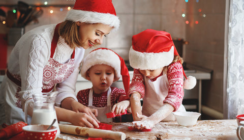 A mom and two young kits are making Christmas sugar cookies wearing Santa hats. The little girl is using a cookie cutter to cut out a shape, while the mom and little boy also hold cookie cutters and watch the little girl.