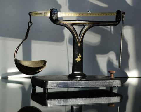 A black iron unequal arm balance sits on a black counter with a shadowy background.