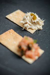 one cracker with salmon tartare and the other cracker with Fjord dip