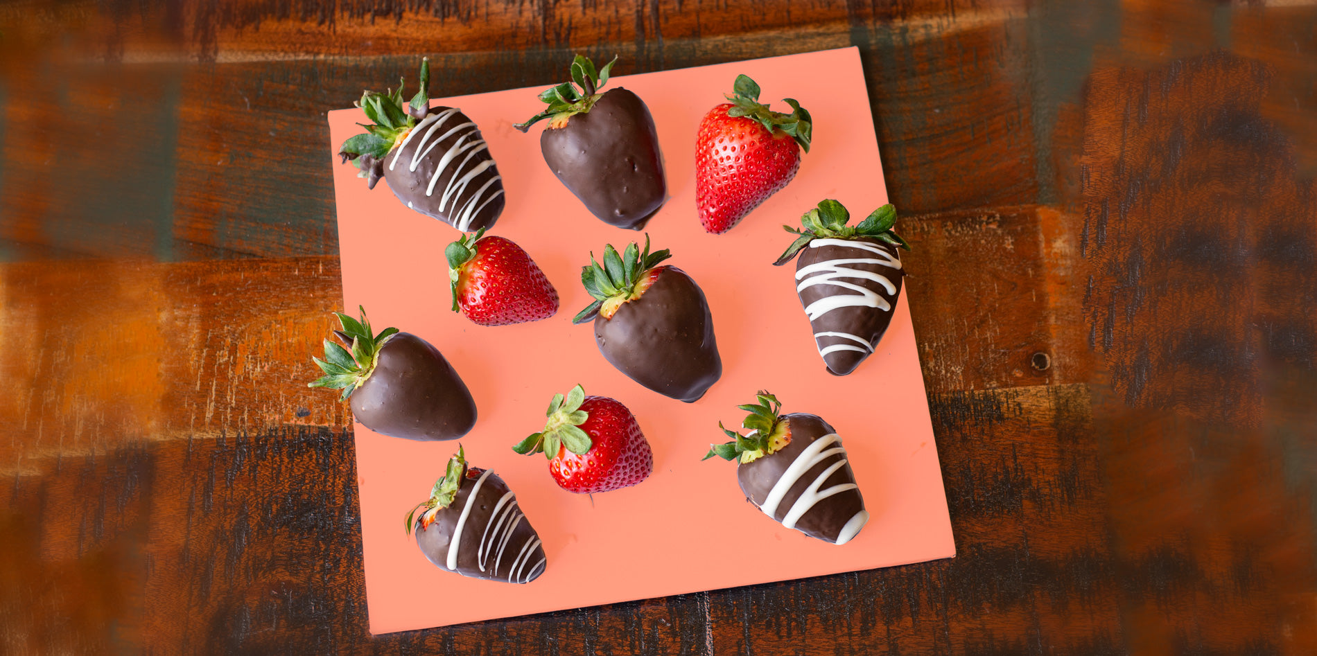 chocolate strawberries on orange board