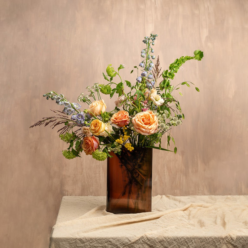 NUDE Mist vase in caramel lead free crystal, paired with tall blooms like delphinium, irises, foliage and grasses, created by Grace & Thorn