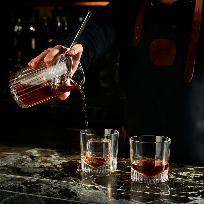 NUDE Caldera whisky glass filled being filled by mixologist in bar