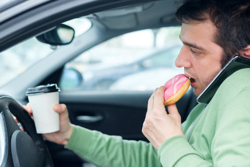 Man eating a donut while driving