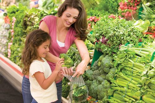 Mother with her daughter buying vegatables