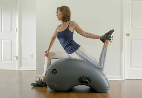 Woman stretching on the Aerotrainer in her home.