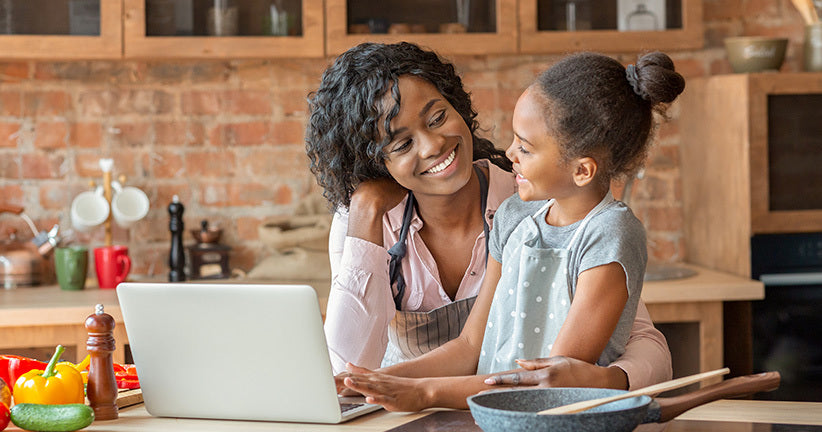 Woman on computer and cooking with her daughter