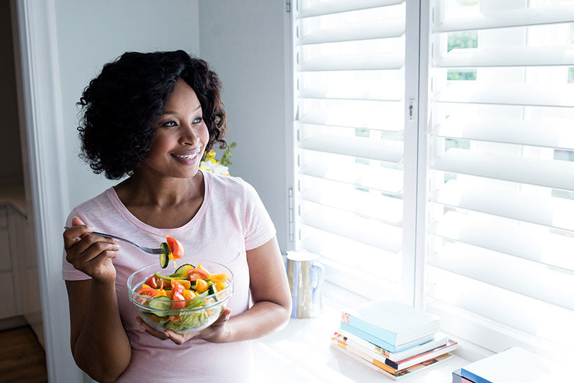 Woman eating a salad and staring out the window