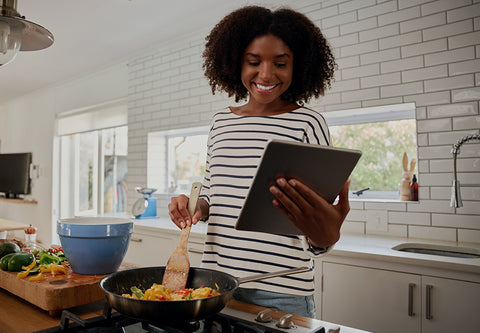 Woman cooking while reading off an ipad.