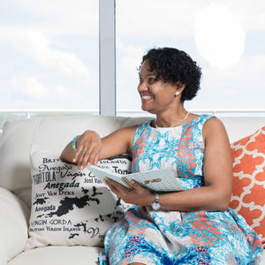 Marva Smith of SunSparkleShine relaxing on a couch with journal in hand.
