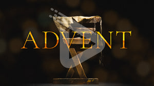 Golden letters spell ADVENT in front of a wooden manger with burlap cloth inside.
