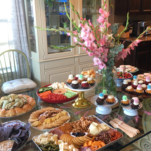a glass dining room table set up buffet style with crudite, cupcakes, and other party snacks with a looming bouquet of pink gladiolas in the center