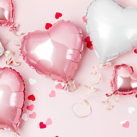 pink and white mylar heart balloons on a pink backdrop with red, white, and pink heart confetti