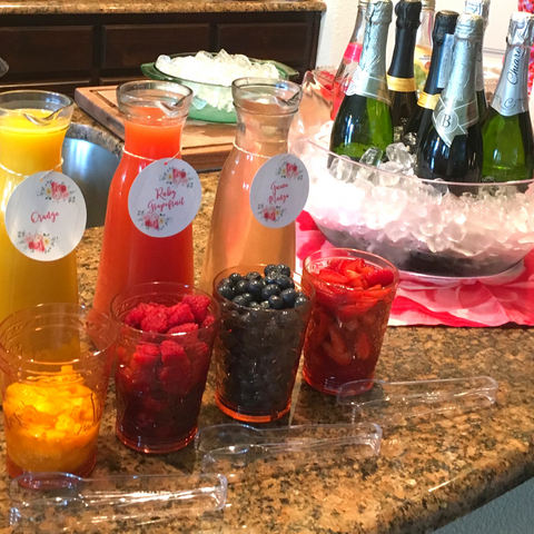 a diy mimosa bar with three carafes of different colored juice and cups of sliced fruit on the left and a large bowl full of ice and wine bottles on the right