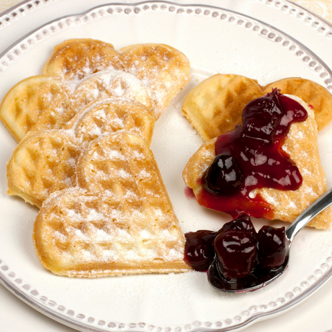 six heart shaped waffles on a white plate, half with powdered sugar, half with Lingonberries