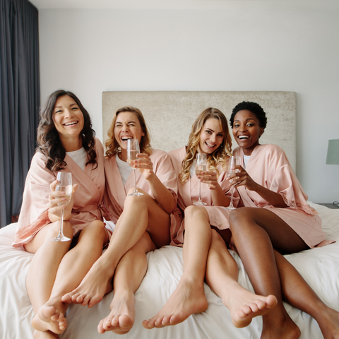 Four women in matching pink robes sit on the edge of a bed holding glasses of champagne