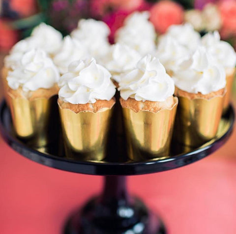a red table top with a glossy black cake stand holding a dozen individual mini cakes in gold foil wrappers topped with whipped cream