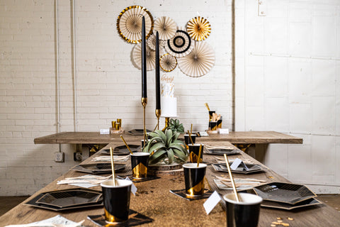 a long head table dressed with black and gold plates and cups for a party, with a set of black, white, and gold party fans on the wall behind them