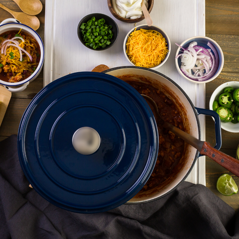 A large blue cast iron pot view from above with the lid half off to show chili inside. Around the pot in a semi circle is an assortment of toppings in small bowls like cheese and onions