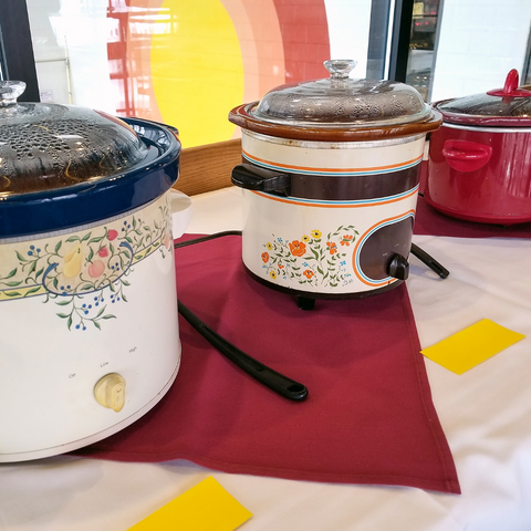 three crock pots on a long table at a chili cook off