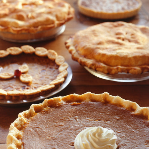A whip cream topped sweet potato pie sits in the foreground with several other topped and decorative crust pies behind it on a wooden table