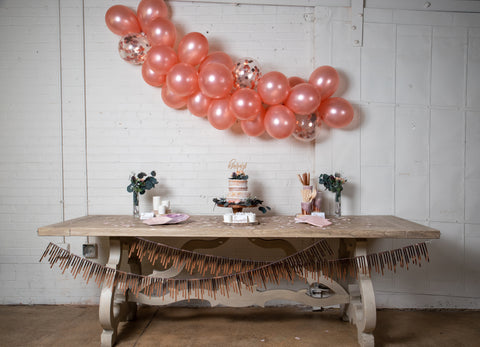 a long table set for a amethyst and rose gold theme party with shimmery streamers along the front, stacks of watercolor plates and napkins, treat cups, a two tiered cake on a wooden stand at the center, eucalyptus arrangements on either end, and a long garland of blush and confetti filled balloons above it