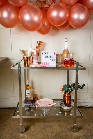 "a metal bar cart styled with copper cups, Eucalyptus, and gem stones- with rose' bottles and a letter board that reads "" stop and smell the rose' """