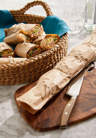 a basket on a grey countertop full of sub sandwiches wrapped in brown paper, sitting behind a cutting board  with one long, uncut wrapped sandwich and knife on it