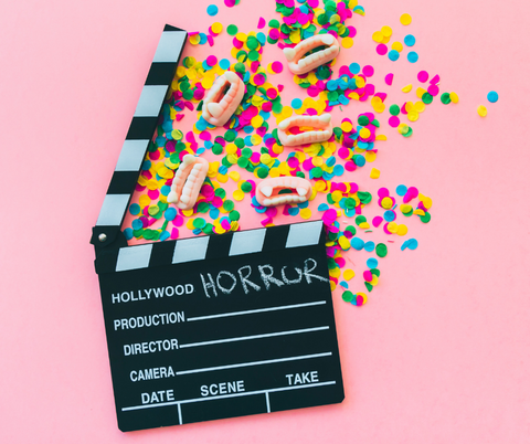movie clapboard on pink background with rainbow confetti and gummy candy vampire fangs