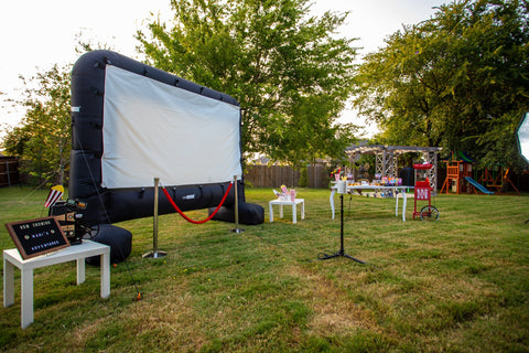 14 foot inflatable outdoor movie screen in backyard with a popcorn machine and party table set up to it's right