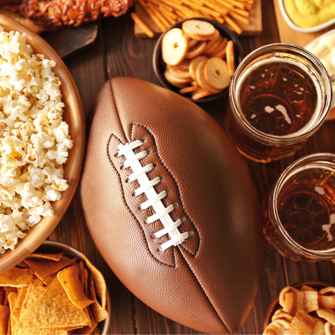 An American football sits laces up, centered on a table surrounded by bar snacks and beer