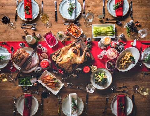 View of a long table from above with 8 place settings and an elaborate holiday feast