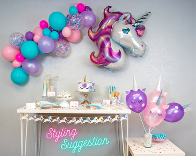 unicorn rainbow party in a box setup with balloon garland