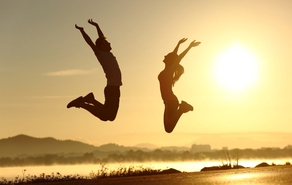 fit couple jumping in the air
