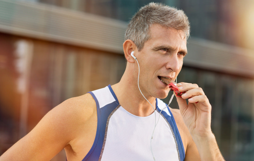 male runner eating chocolate energy bar
